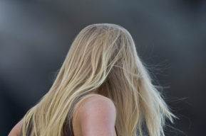 Blond long-haired young lady woman watching the surfers at Morro
